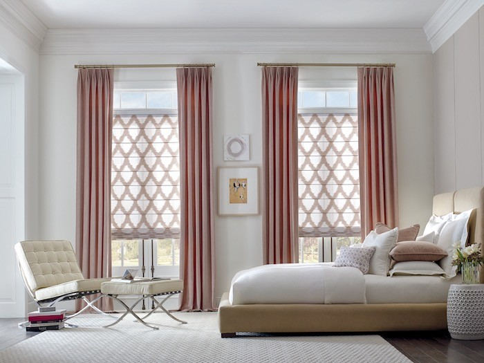 A bedroom with rose colored window coverings